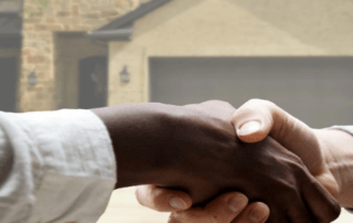 People shaking hands in front of house