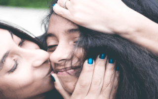 Mum kissing daughter on cheek