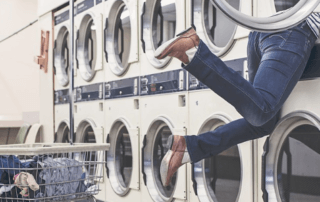 legs dangling out of washing machine at laundromat