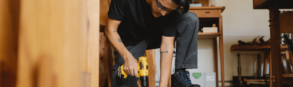 man drilling into wood